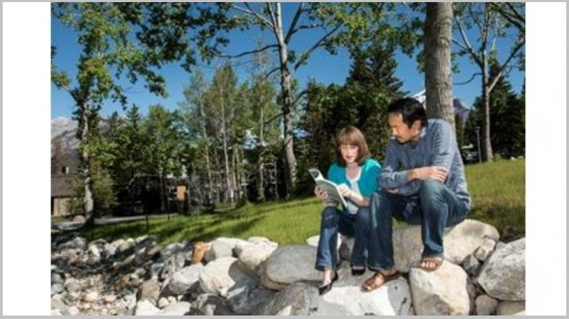 Lesende mann og kvinne på steiner foran trær.foto