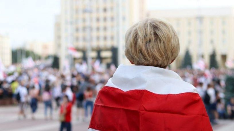 Kvinne bakfra med belarusisk flagg over skuldrene
